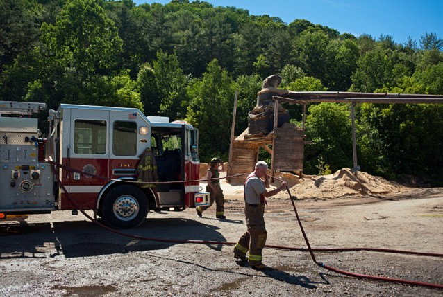 June Willie Franklin, right, of Royalton empties a fire hose while cleaning up the scene after seven area fire departments responded to an industrial fire at the DCI Corporation sawmill in Royalton. (Herald / Seth Butler)