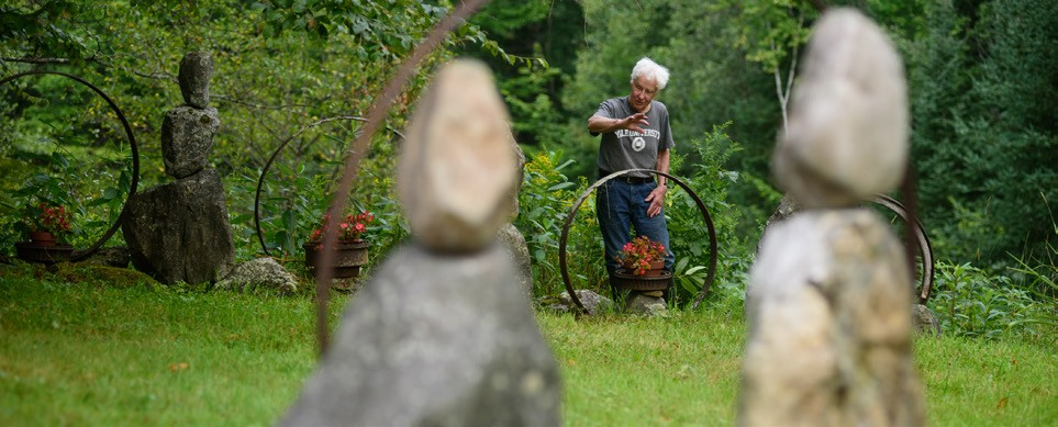 August Robert Finkle show some of the many sculptural compositions he has created on his property in Rochester. (Herald / Tim Calabro)