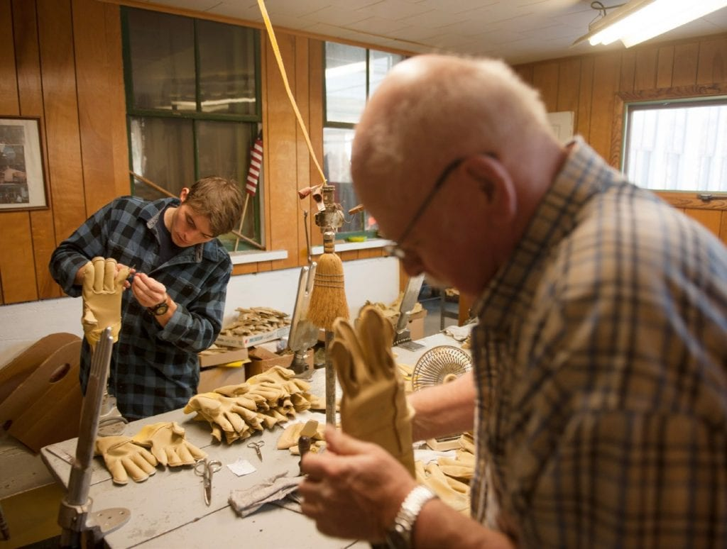 January Sam Hooper, left, and Kurt Haupt steam gloves together. The leather gloves are pulled onto heated hand forms in order to soften the material. Hooper purchased the storied Green Mountain Glove Factory from the Haupt family. (Herald / Bob Eddy)